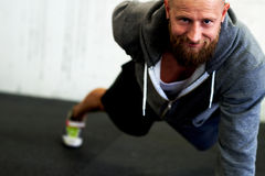 Athletic man smiling at camera doing one arm pushup Stock Photography