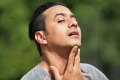 Athletic Man With Sore Throat. A handsome adult hispanic man Royalty Free Stock Image