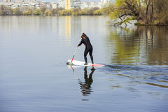 Athletic man stand up paddle board SUP. Athletic man in a diving suit stand up paddle board on a background of the city stock image