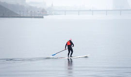 Athletic man stand up paddle board SUP03. Athletic man in a diving suit stand up paddle board on the river in the city SUP Royalty Free Stock Images