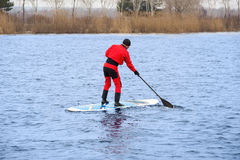 Athletic man stand up paddle board SUP. Athletic man in a diving suit stand up paddle board on the river in the city stock photo