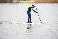Athletic man stand up paddle board SUP. Athletic man in a diving suit stand up paddle board on the river in the city royalty free stock image