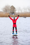 Athletic man stand up paddle board SUP. Athletic man in a diving suit stand up paddle board on the river in the city royalty free stock photos