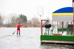 Athletic man stand up paddle board SUP. Athletic man in a diving suit stand up paddle board on the river in the city stock image