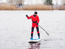 Athletic man stand up paddle board SUP. Athletic man in a diving suit stand up paddle board on the river in the city stock photography