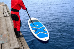 Athletic man stand up paddle board SUP. Male kayaker prepares to sail from a wooden pier royalty free stock photography