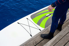 Athletic man stand up paddle board SUP. A man is standing on a wooden pier with a sup. The legs are visible stock image