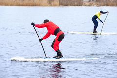 Athletic man stand up paddle board SUP. Two athletic men in a diving suit stand up paddle board on the river in the city royalty free stock photo