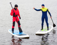 Athletic man stand up paddle board SUP. Two athletic men in a diving suit stand up paddle board on the river in the city royalty free stock images