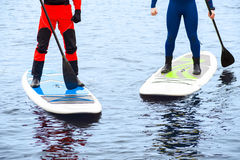 Athletic man stand up paddle board SUP. Two athletic men in a diving suit stand up paddle board on the river in the city royalty free stock photos