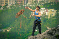 Athletic man standing on cliff with rope in hands Stock Image