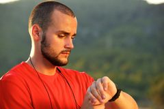 Athletic man standing outside checking watch Royalty Free Stock Photography