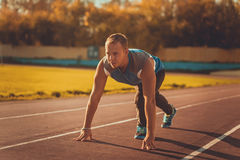 Athletic man standing in posture ready to run on a treadmill. Stock Image