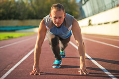 Athletic man standing in posture ready to run on a treadmill. Royalty Free Stock Photography