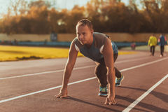 Athletic man standing in posture ready to run on a treadmill Royalty Free Stock Photos