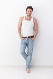 Athletic man standing at wall. Athletic young man standing at wall, wearing jeans and undershirt royalty free stock images