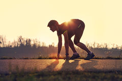 Athletic man starting evening jogging in sun rays Royalty Free Stock Image