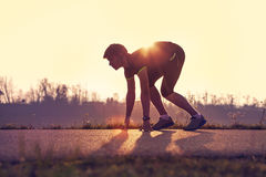 Athletic man starting evening jogging in sun rays Royalty Free Stock Images