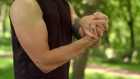 Athletic man stretching hands. Guy warm up wrist in park. Fit boy training
