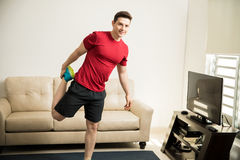 Athletic man stretching up his legs at home Stock Images