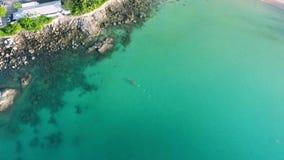 Athletic man swimming on long kayak in blue water near rocks. HD aerial view. Phuket, Thailand. stock footage