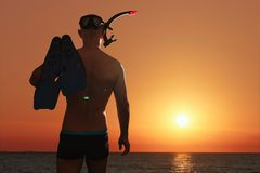 An athletic man with a swimming mask, snorkel and flippers enters the sea. He is going to do free diving. stock photos
