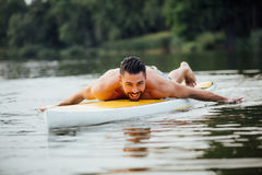 Athletic man swimming on a paddleboard royalty free stock images