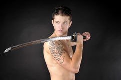 Athletic man with sword. Athletic man with sword - isolated on dark background Royalty Free Stock Photography