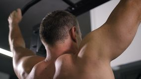Athletic man without a T-shirt pulls up on the bar. Close up back muscles 4K Slow Mo stock video