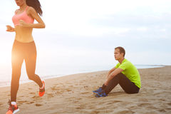 Athletic man taking a break while his girlfriend exercising Stock Photo