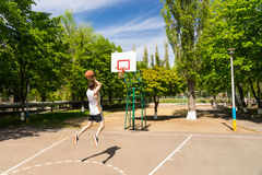 Athletic Man Taking Jump Shot on Basketball Court Stock Photography