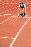 Athletic man on track, all set for race. Royalty Free Stock Photo