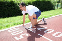 Athletic man on track starting to run Royalty Free Stock Images