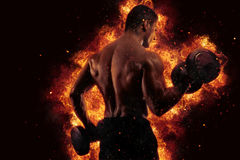Athletic man training biceps at the gym with fire effect. Athletic muscular man training biceps at the gym with fire effect Stock Photos