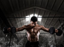 Athletic man training biceps at the gym. Athletic muscular man training biceps with dumbbells at the gym Stock Photography