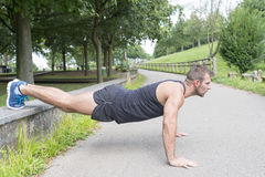 Athletic man training and doing push ups, outdoor. royalty free stock images