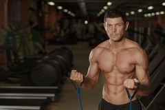 Athletic man training in fitness club, front view royalty free stock images