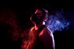 Athletic man in training mask. A young athletic man in a sports shirt breathes through a training black mask around a blue and red smoke cloud from a vape on a Stock Photos