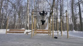 Athletic man training pull up exercise on winter gym workout on sport ground. Young man exercising pull ups for body training on winter sport ground stock video footage