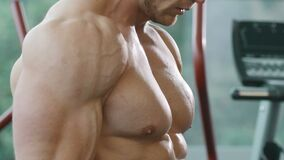 Athletic man training pumping up biceps muscles