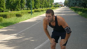Athletic man training on running track using wearable tracker gadget stock footage