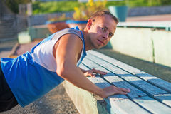 Athletic man trains, pushed from the bench on stadium. concept of health and strength. Stock Photos