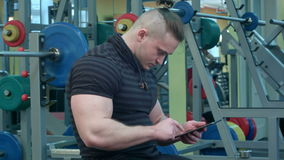 Athletic man using digital tablet in the gym stock footage
