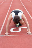 Athletic man waiting in starting block. In a stadium Royalty Free Stock Photography