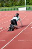 Athletic man waiting in starting block. In a stadium Royalty Free Stock Images