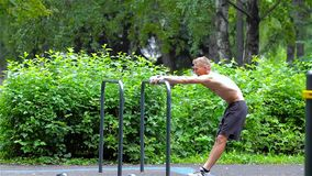Athletic man warming up in City Park. side view. Workout. stock video footage