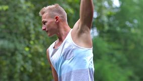 Athletic man warming up before exercise in City Park under summer trees for sport fitness. hand stock footage