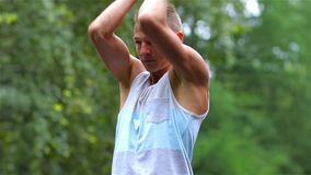 Athletic man warming up before exercise in City Park under summer trees for sport fitness. hand stock video footage