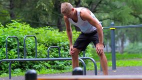 Athletic man warming up before exercise in City Park under summer trees for sport fitness. legs stock video