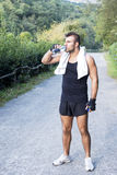 Athletic man with water bottle after his exercising outdoor. Stock Photo
